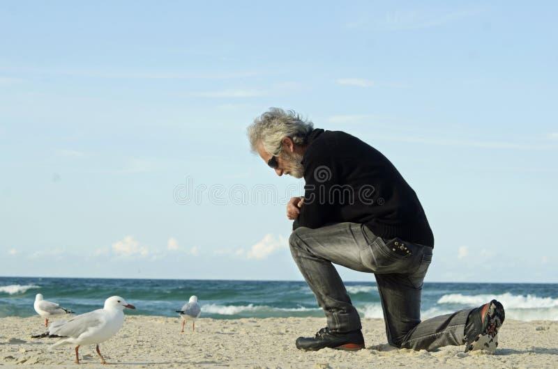 Hombre solo triste desesperado que ruega solamente en la playa del océano fotografía de archivo