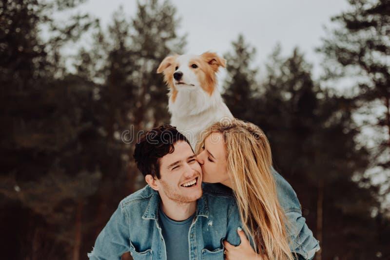 Hombre sonriente alegre feliz con la muchacha y el perro en el suyo detrás besar los pares de la gente joven en trajes del dril d imagenes de archivo