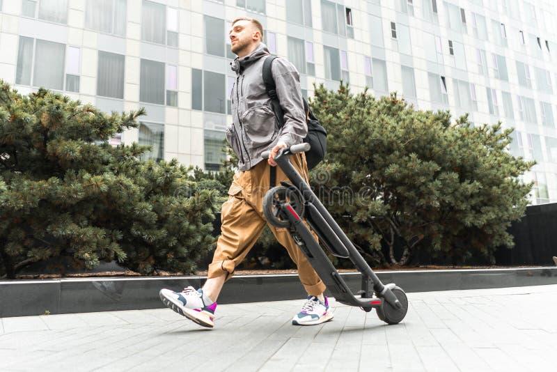 Hombre sonriente atractivo joven que sostiene la vespa eléctrica del retroceso mientras que va para un paseo en la calle fotos de archivo