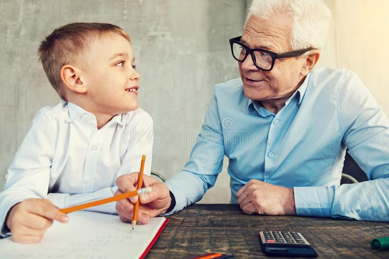 Hombre sonriente bueno que ayuda a su pequeño nieto fotografía de archivo