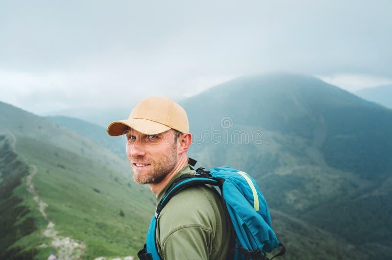 Hombre sonriente cansado del backpacker en gorra de béisbol que camina por la trayectoria nublada de niebla de la cordillera del  fotos de archivo libres de regalías