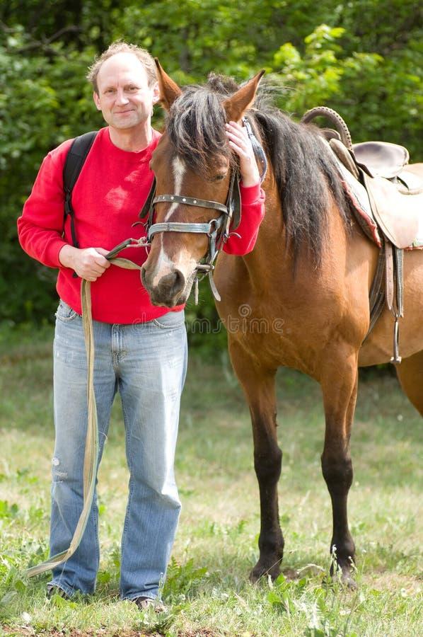 Hombre sonriente con el caballo en el bosque fotografía de archivo libre de regalías