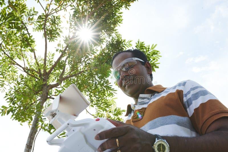 Hombre sonriente con el control remoto foto de archivo libre de regalías