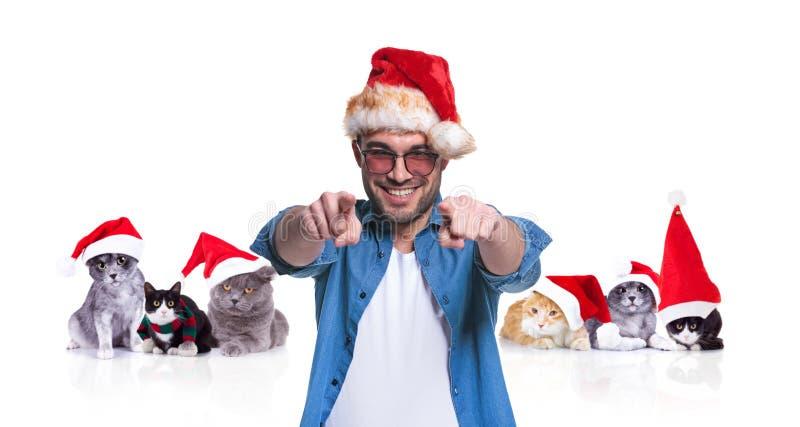 Hombre sonriente con el finger de los puntos del casquillo de santa cerca de gatos de la Navidad imagenes de archivo