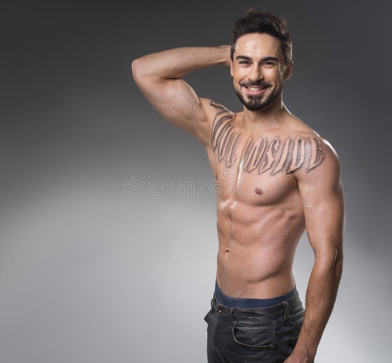 Hombre sonriente con el tatuaje que se coloca desnudo fotos de archivo libres de regalías
