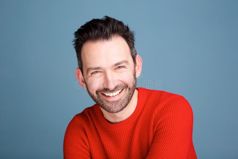 Hombre sonriente con la barba que presenta contra fondo azul imagen de archivo libre de regalías