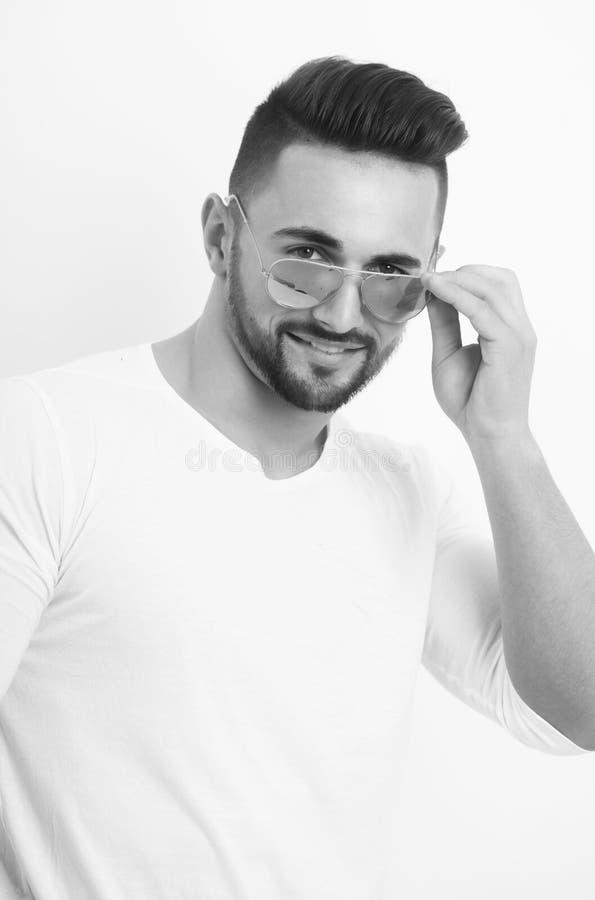 Hombre sonriente con la barba que presenta en gafas de sol tipo aviador retras de moda fotos de archivo libres de regalías