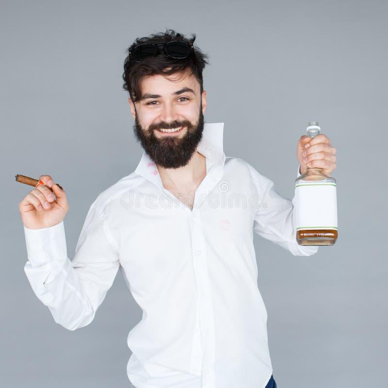 Hombre sonriente con la barba que sostiene una botella de whisky fotografía de archivo