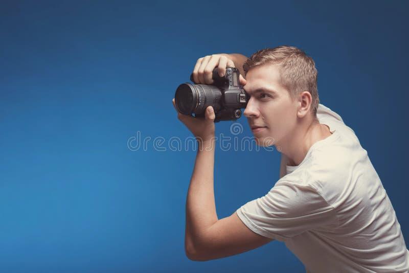 Hombre sonriente con la cámara aislada en fondo azul Cámara digital de la tenencia del hombre joven y foto de la fabricación que  imagen de archivo libre de regalías