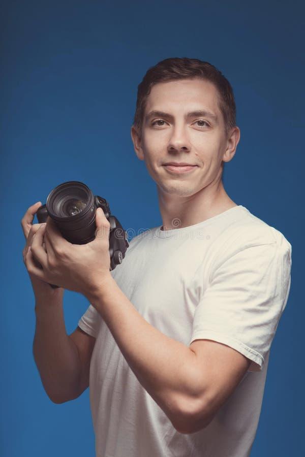 Hombre sonriente con la cámara aislada en fondo azul Cámara digital de la tenencia del hombre joven y foto de la fabricación que  fotografía de archivo