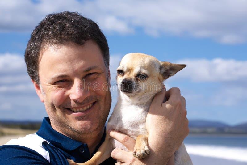 Hombre sonriente con la chihuahua en la playa fotos de archivo libres de regalías