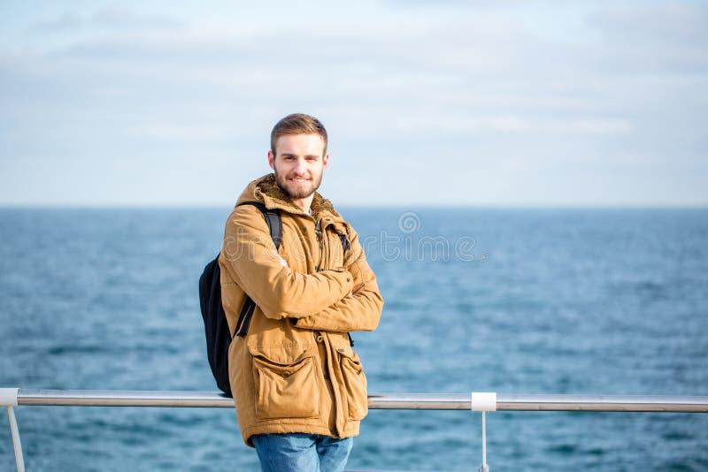 Hombre sonriente con la mochila que camina cerca del mar foto de archivo libre de regalías