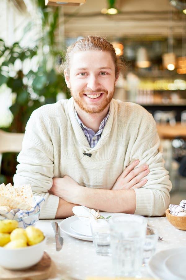 Hombre sonriente con las manos cruzadas que se sientan en café foto de archivo libre de regalías