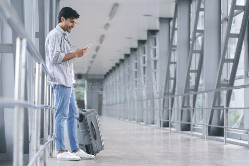 Hombre sonriente con mensajería del equipaje en su teléfono móvil en el aeropuerto imagenes de archivo