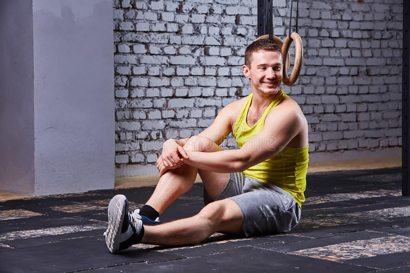 Hombre sonriente del atleta en el sportwear asentado en el piso en el gimnasio apto de la cruz que tiene un resto después de entr foto de archivo
