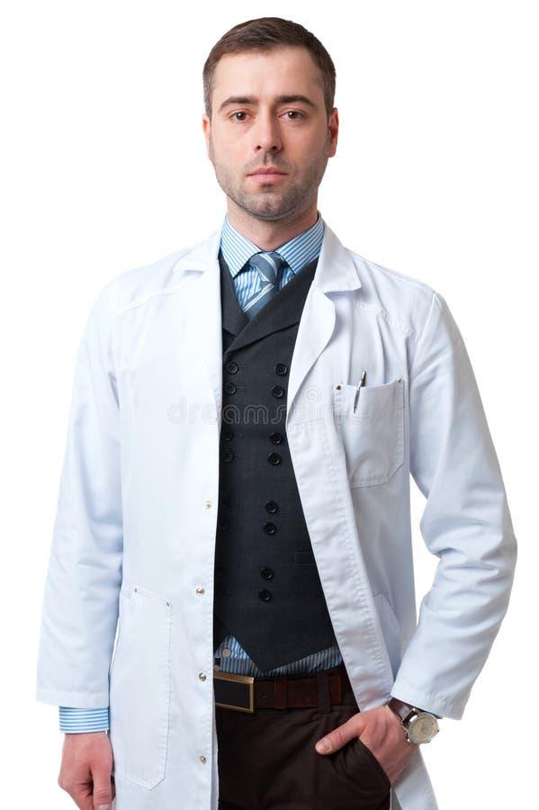 Hombre sonriente del doctor con la mano en el bolsillo aislado en el backgro blanco foto de archivo libre de regalías
