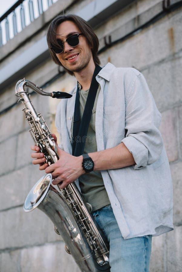 Hombre sonriente del inconformista en las gafas de sol que sostienen el saxofón foto de archivo libre de regalías