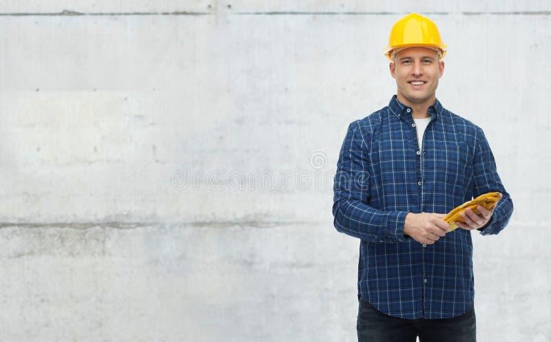 Hombre sonriente en casco con los guantes fotografía de archivo