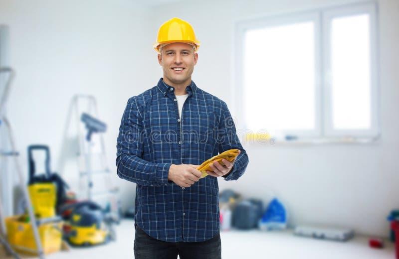 Hombre sonriente en casco con los guantes sobre sitio fotografía de archivo libre de regalías