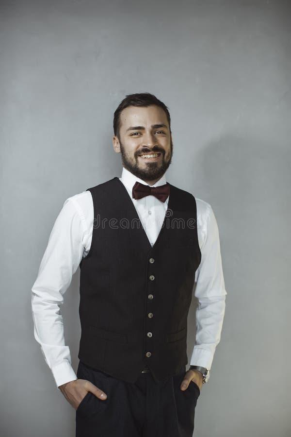 Hombre sonriente en chaleco y corbata de lazo negros imagen de archivo libre de regalías