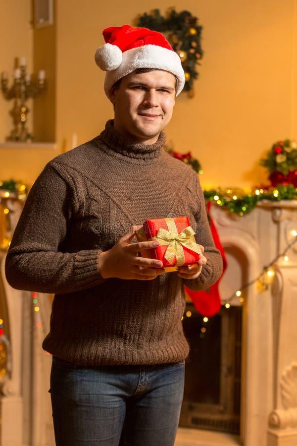 Hombre sonriente en el sombrero rojo de Papá Noel que celebra la caja de regalo roja en la casa fotos de archivo