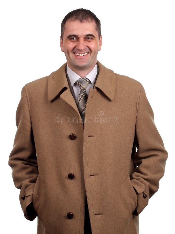 Hombre sonriente en la capa marrón clara aislada en blanco fotografía de archivo libre de regalías
