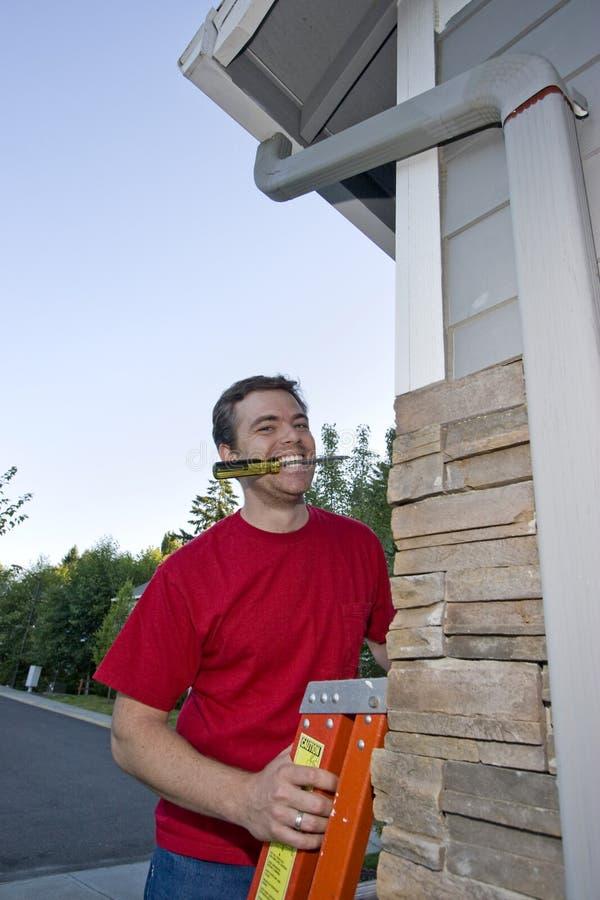 Hombre sonriente en la escala - vertical fotografía de archivo