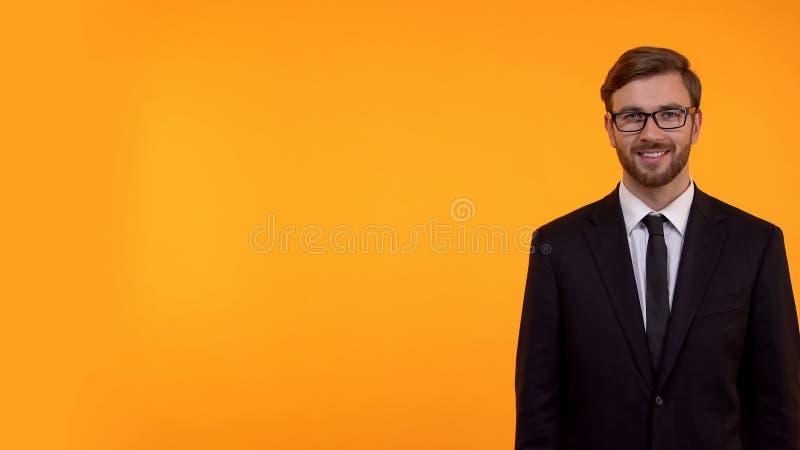Hombre sonriente en la situaci?n del traje en el fondo amarillo, lugar para su texto, plantilla fotografía de archivo