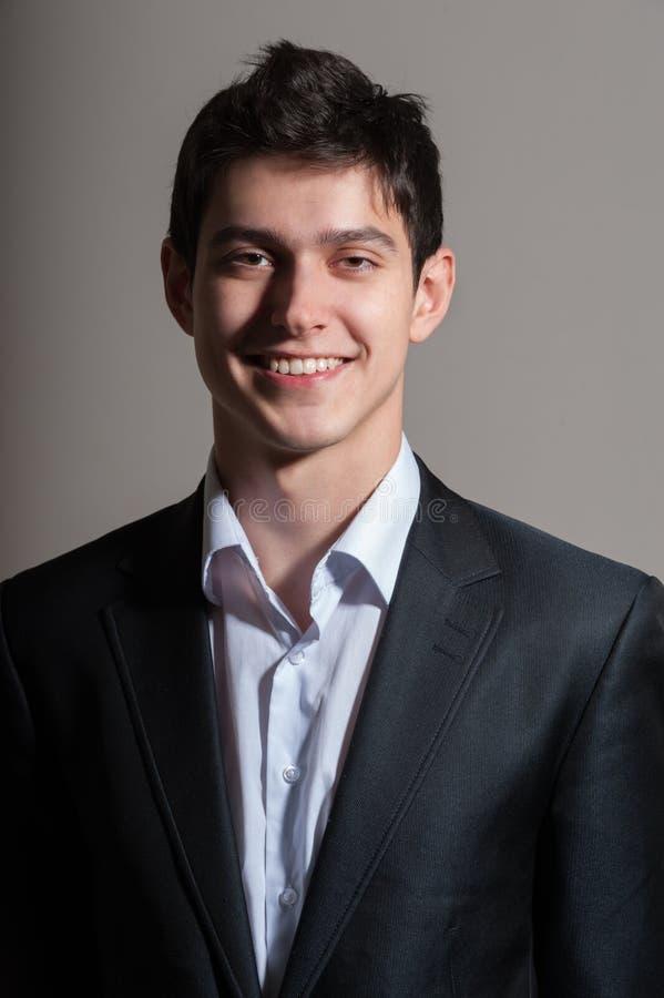 Hombre sonriente en traje en fondo gris imagen de archivo libre de regalías