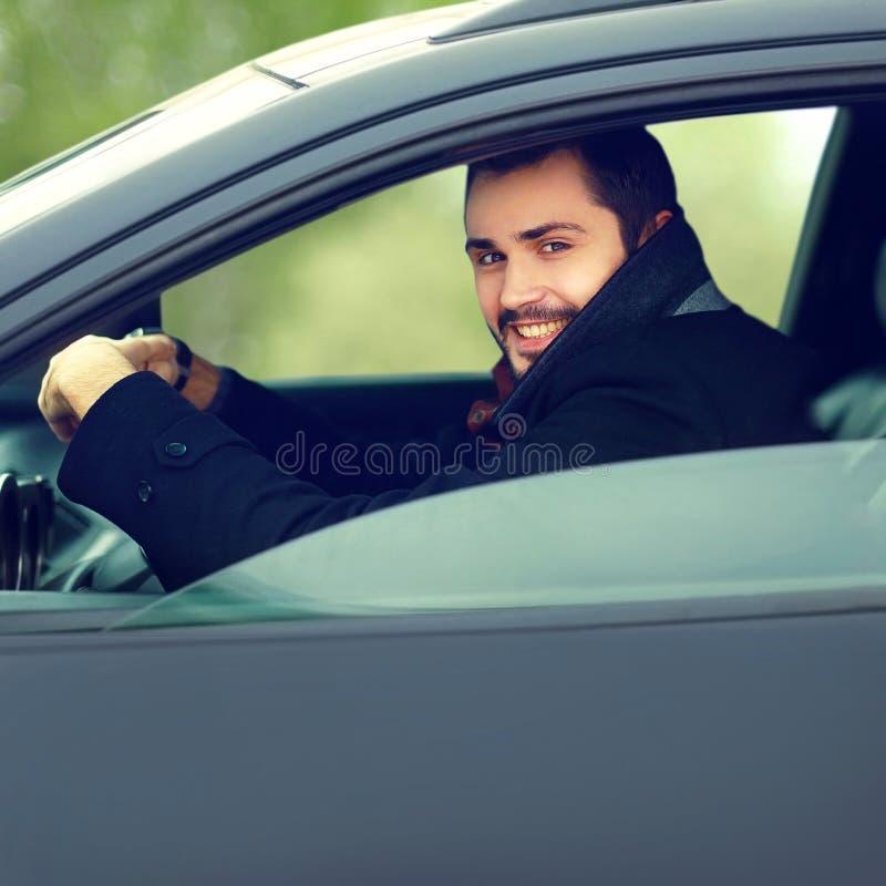 Hombre sonriente feliz del conductor detrás de la rueda de su coche imagenes de archivo