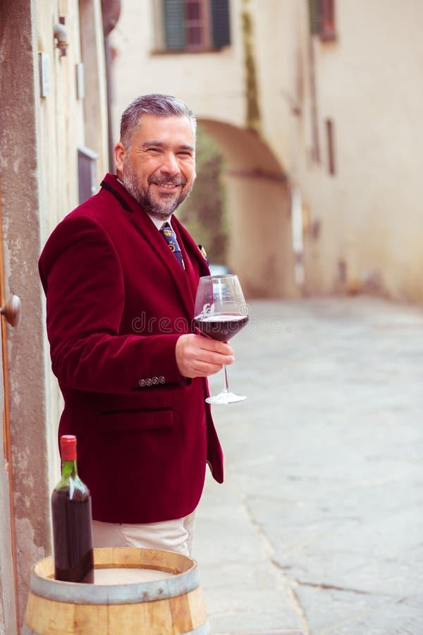 Hombre sonriente feliz maduro con el vidrio de vino rojo al aire libre en pueblo italiano viejo fotos de archivo
