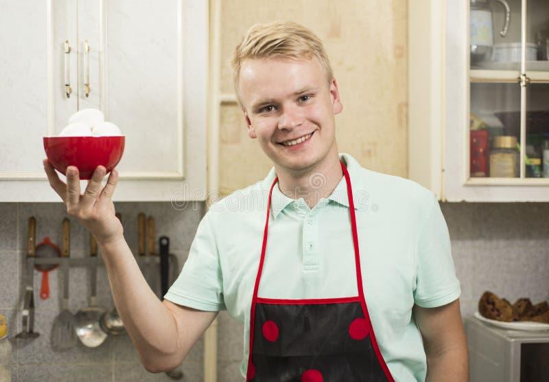 Hombre sonriente feliz que se coloca en cocina con la placa de huevos fotos de archivo libres de regalías