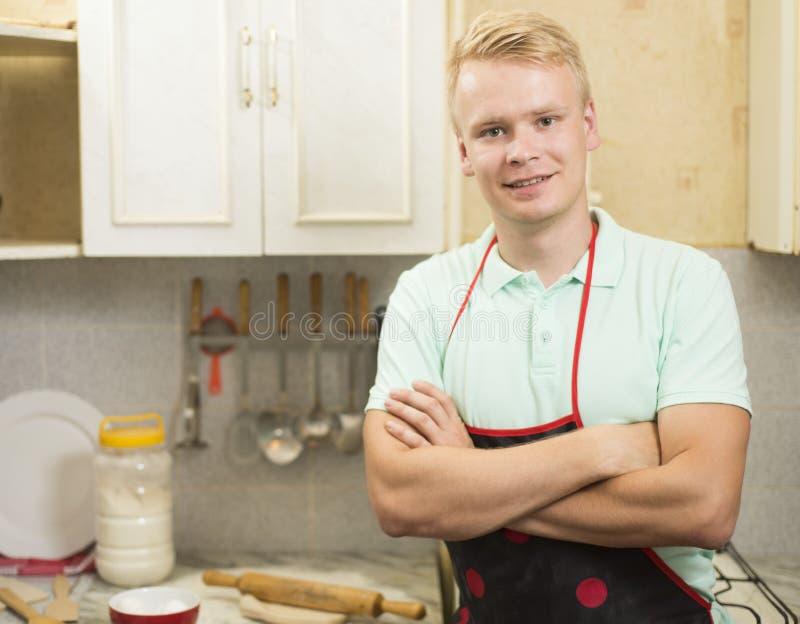 Hombre sonriente feliz que se coloca en la cocina con las manos dobladas fotografía de archivo