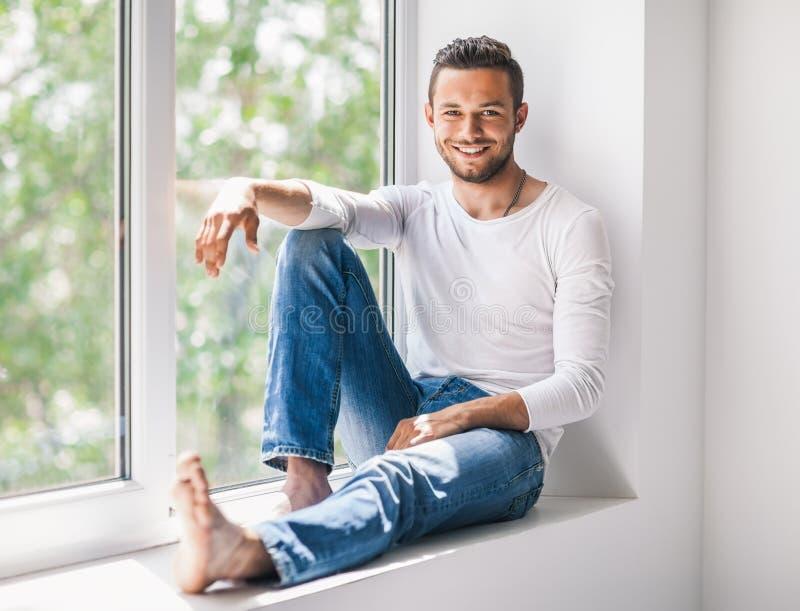 Hombre sonriente feliz que se relaja en travesaño de la ventana imágenes de archivo libres de regalías