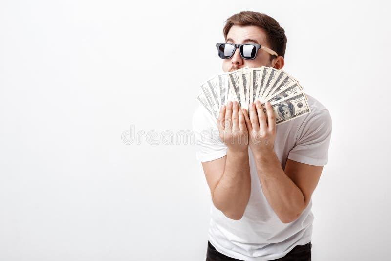 Hombre sonriente hermoso con la barba en la camisa que lleva a cabo mucho hundre foto de archivo libre de regalías