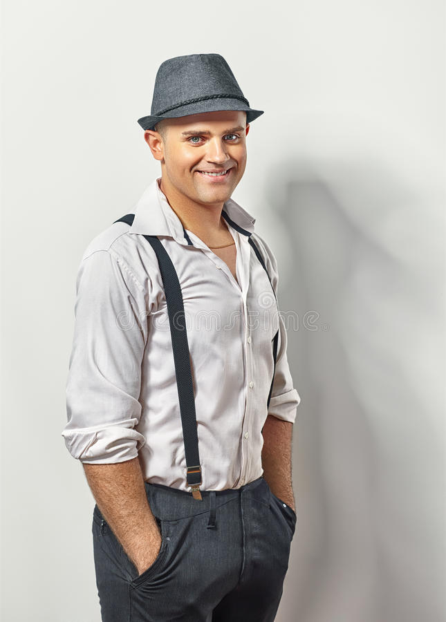 Hombre sonriente hermoso en sombrero y ligas fotos de archivo libres de regalías