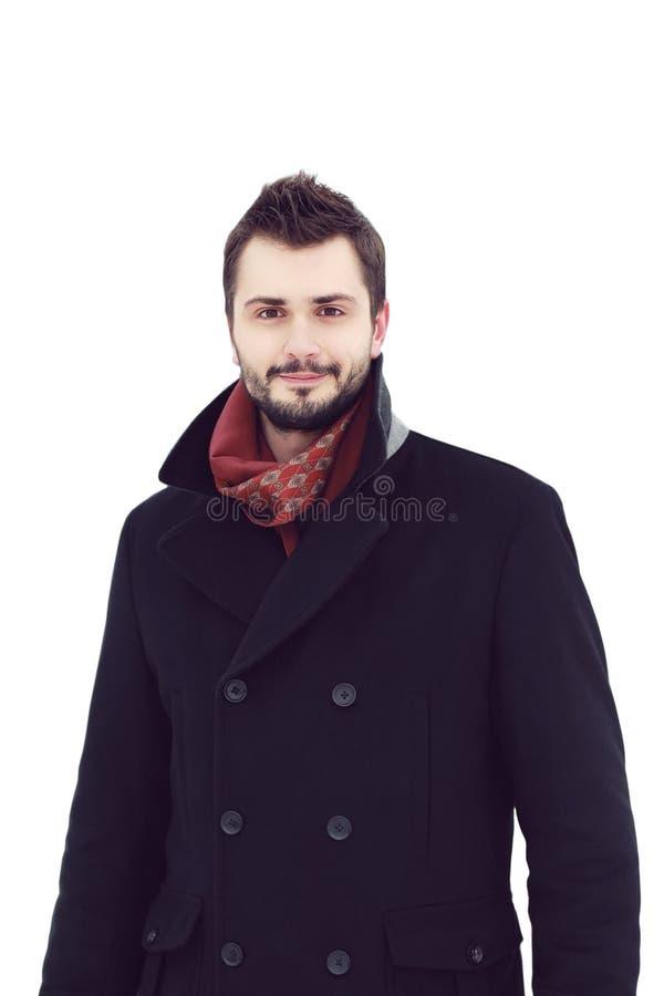 hombre sonriente hermoso en una capa aislada en el fondo blanco imagen de archivo libre de regalías