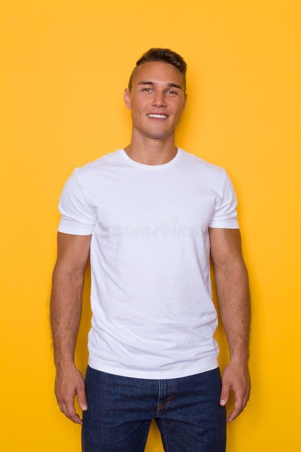 Hombre sonriente hermoso joven en la camiseta blanca fotografía de archivo