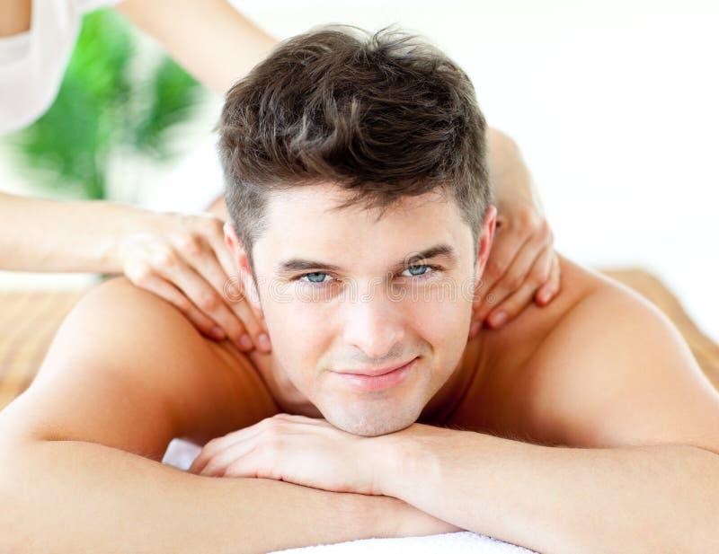 Hombre sonriente hermoso que disfruta de un masaje posterior foto de archivo
