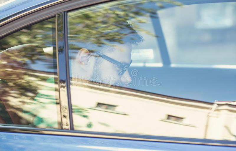 Hombre sonriente hermoso que se sienta en un asiento trasero en el coche fotos de archivo libres de regalías