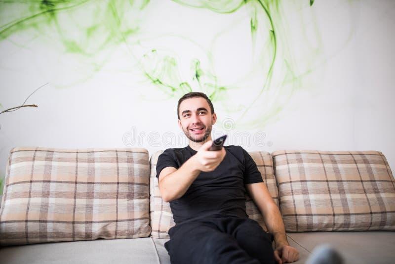 Hombre sonriente hermoso que se sienta en un sofá con un teledirigido en su mano foto de archivo