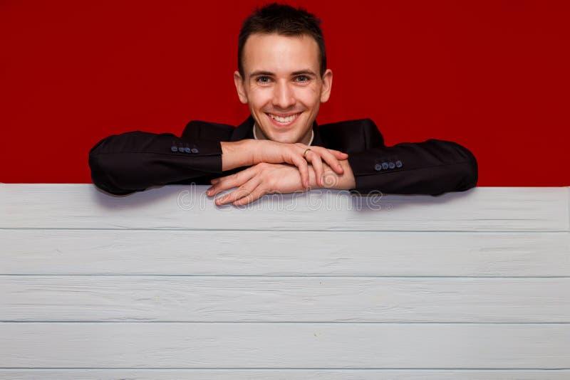 Hombre sonriente joven con el tablero rojo en blanco de la muestra Bandera hermosa de la tenencia del hombre de negocios con el c foto de archivo libre de regalías