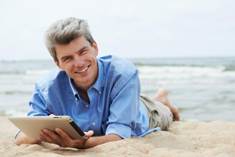 Hombre sonriente joven con PC de la tablilla en la costa fotografía de archivo