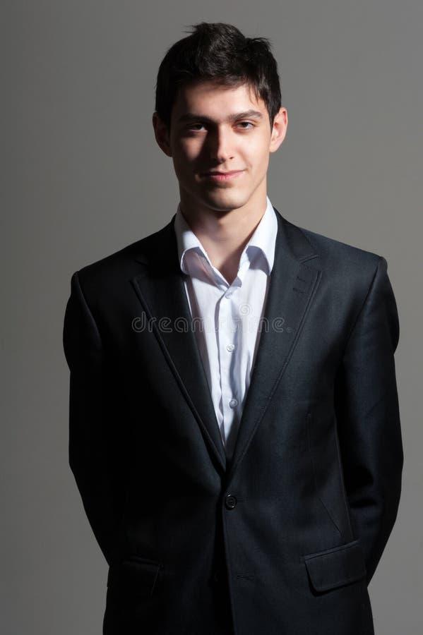 Hombre sonriente joven de la persona del negocio en traje en fondo gris foto de archivo libre de regalías