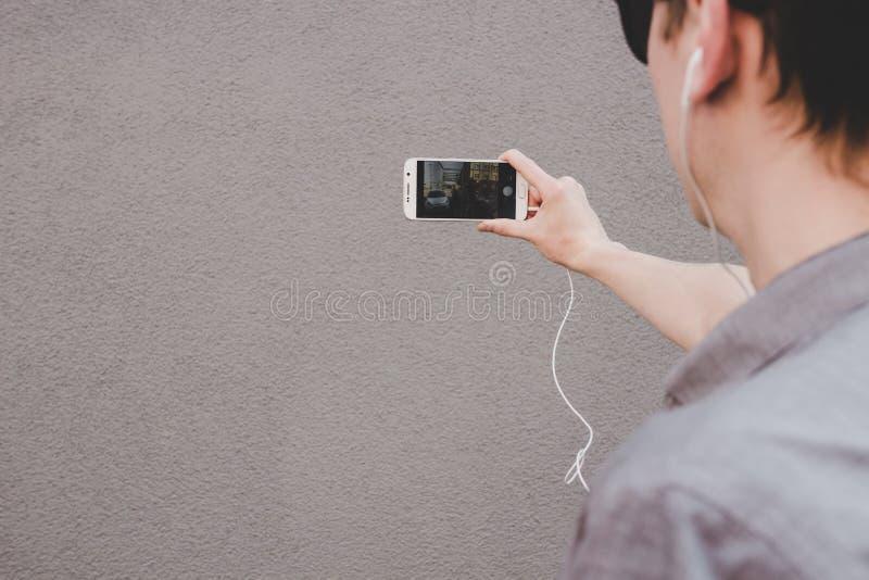 Hombre sonriente joven del inconformista que toma el selfie con su smartphone y mirando la cámara con la atención foto de archivo