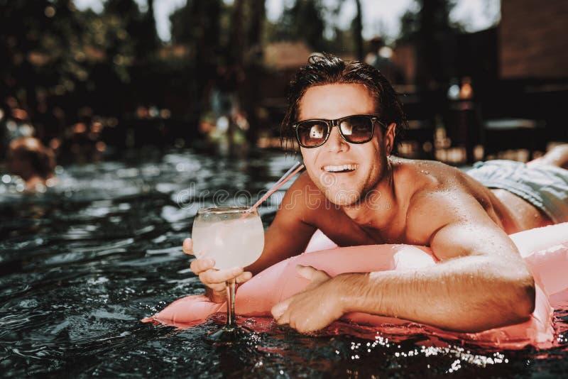 Hombre sonriente joven en gafas de sol en el colchón de aire imagen de archivo libre de regalías