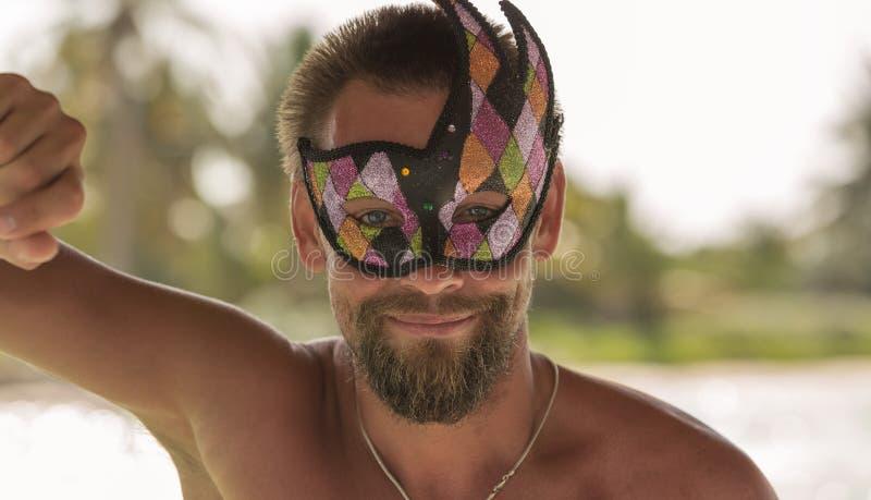 Hombre sonriente joven en máscara del dominó imagen de archivo libre de regalías