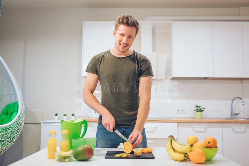 Hombre sonriente joven que cocina las frutas frescas en la cocina Alimento sano Comida vegetariana Detox de la dieta imagen de archivo