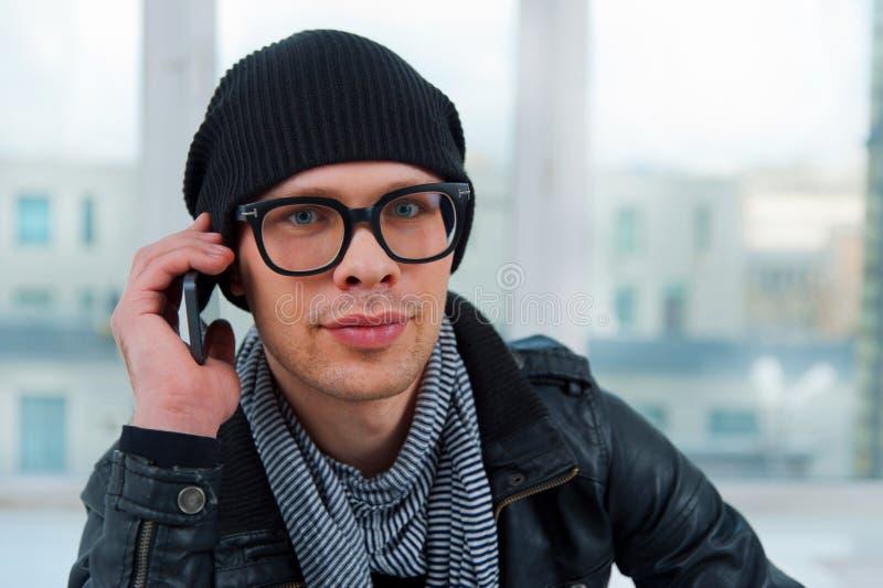 Hombre sonriente joven que habla en el teléfono imagen de archivo libre de regalías