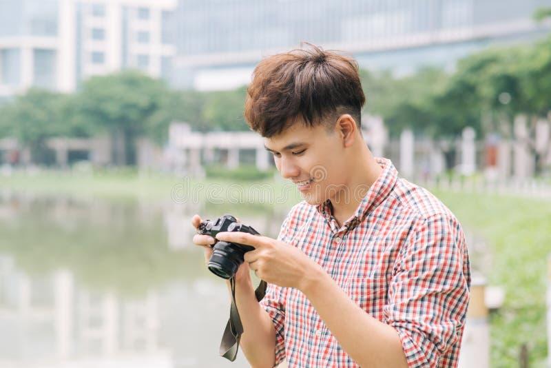 Hombre sonriente joven que toma la imagen mientras que camina por la ciudad imagen de archivo